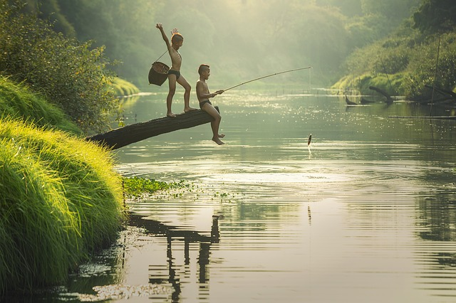 Two happy Asian kids fishing, Indonesian river - WOIMA Corporation